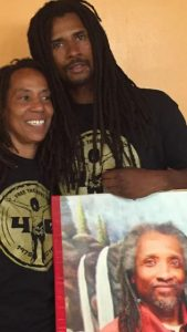 Debbie Africa, with son Mike Africa Jr. with photo of still imprisoned husband/father Mike Africa Sr