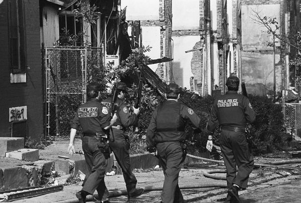 Heavily armed police patrol the just-bombed area of Philadelphia.
